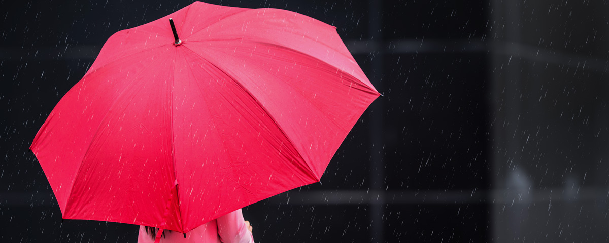 Person standing under a red umbrella, the symbol for sex workers